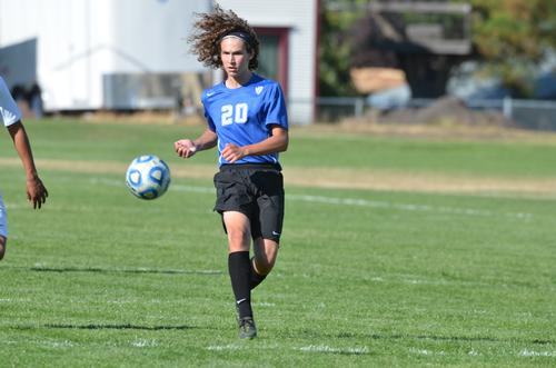 LHS Soccer player kicking ball down the field, nice sunny day